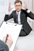 stock photo of psychologist  - Young man wearing a black suit sitting on a couch shouting nervous explaining his problems - JPG