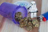 stock photo of trooper  - Hybrid on the Indica dominant side Skywalker OG Medicinal Medical Marijuana with white storm trooper, blue lighter and purple plastic medicine bottle. ** Note: Shallow depth of field - JPG