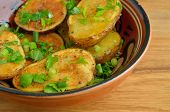 pic of oven  - Rustic oven baked potatoes with herbs on wooden table - JPG
