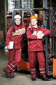 image of forklift  - happy smiling warehouse workers in uniform in front of forklift stacker loader - JPG