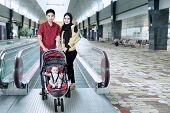stock photo of escalator  - Portrait of muslim family standing in the airport hall near the escalator with baby on the pram - JPG
