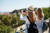 picture of two women taking cell phone  - Couple tourists taking photo landscape with camera phone on park - JPG