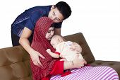 foto of she-male  - Young man kiss his wife when she kiss their baby isolated on white background - JPG