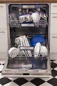 pic of dishwasher  - Dishwasher loades in a kitchen with clean dishes and blue light - JPG