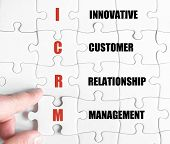 stock photo of customer relationship management  - Hand of a business man completing the puzzle with the last missing piece - JPG