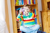 picture of daycare  - Active kid boy making photos with photocamera indoors - JPG