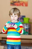 stock photo of daycare  - Active kid boy making photos with photocamera indoors - JPG