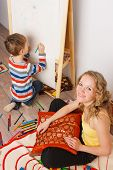 stock photo of little boys only  - Young woman sitting on floor in children room while little boy drawing on easel - JPG