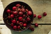 stock photo of black-cherry  - Bowl with black cherry rustic selective focus horizontal top view - JPG