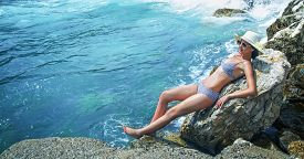 image of sunbathers  - Young pretty woman on the beach sunbathing. Summer travel. Sea - water wellbeing.