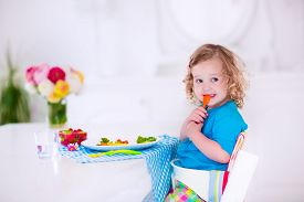 image of daycare  - Child having vegetables for lunch - JPG
