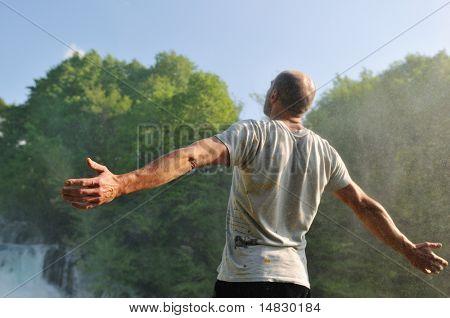 Постер, плакат: стоя человек с широко открытой оружие с водопадами в фоновом режиме и представляющих свежесть здоровых , холст на подрамнике