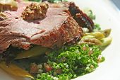 Roast beef with garnishing on white plate