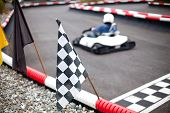picture of karts  - moving car and flags on karting track - JPG