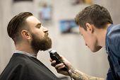 Young Man Getting Beard Grooming At Barbershop poster