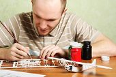Man Assembling Plastic Airplane Model And Painting Pieces