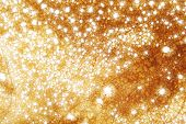 stock photo of gold glitter  - golden glitter sparkles dust background super macro shallow DOF - JPG