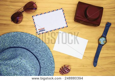 poster of Blank White Postcard And Air Mail Envelope On Wooden Table. Travel Card Top View With Travel Accesso
