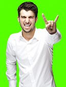 portrait of young man gesturing rock symbol against a removable chroma key background