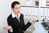 Pretty caucasian businesswoman gesturing don`t know what to do.
