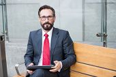 Relaxed Businessman In Glasses Using His Pc Tablet While Sitting On Bench. Senior Businessman Using  poster