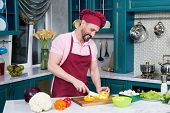 Aged Guy In Apron And Cap Cutting Yellow Paprika For Salad On Cutting Board By Knife. Chef Cooking V poster
