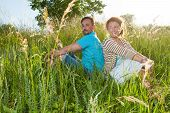 Couple In Big Green Grass Back To Back. Man And Woman Sitting In The Field In Summer Day. Loving Cou poster