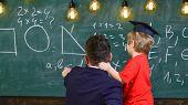 Boy, Child In Graduate Cap Listening Teacher, Chalkboard On Background, Rear View. Teacher With Bear poster