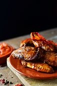 closeup of some barbecue chicken wings in an earthenware plate and a bowl with barbecue sauce on a r poster