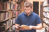 Portrait Of A Man Reading A Book Standing In A Public Old Library. Book Search In The Library. Self- poster