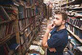Portrait Of A Man With A Beard Standing On The Background Of An Atmospheric Public Library And Looki poster