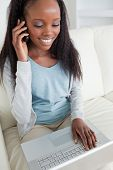 Close up of smiling woman on the phone while using notebook