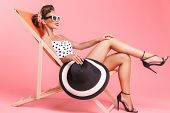 Photo of young pin-up woman isolated over pink background wall in swimwear on beach chair. poster