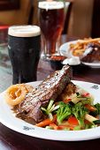 stock photo of guinness  - 10 oz. New York Striploin Angus steak topped with Irish whiskey gravy saut