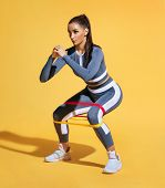 Sporty Woman Squatting Doing Sit-ups With Resistance Band. Photo Of Latin Woman In Fashionable Sport poster