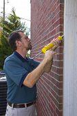 Contractor Filling Exterior Wall Cracks