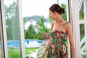Beautiful young woman daydreaming while standing near door