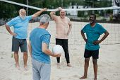 Multicultural Old Friends Playing Volleyball On Beach On Summer Day poster
