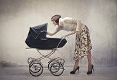 Young mother cuddling her baby lying in a pram