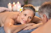 Smiling couple lying naked on massage table at spa looking at each other. Happy senior couple enjoyi poster