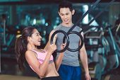 Side view of a fit and cheerful young woman doing ring biceps curl exercise during functional traini poster
