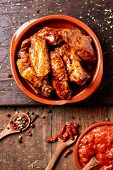 high angle view of some barbecue chicken wings in an earthenware plate and a bowl with barbecue sauc poster