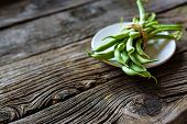 Green String Beans In A Bowl On Rustic Wooden Table poster