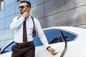 Handsome Security Guard Listening Message With Security Earpiece On Street And Opening Car poster