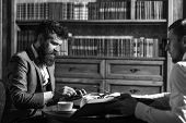 Man In Suit Or Journalist With Friend In Library. Journalism Concept. Man With Beard Interviews Writ poster