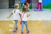 Two Cute Blond Little Girls Walking Together In Mall. Pair Of Kid Friends Holding Hands During Walk. poster