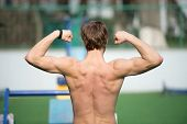 Proud Of His Shape. Man Athlete Training Outdoor Shows His Muscular Back. Athletic Man Posing With M poster