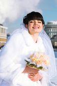 novia feliz y hermosa sonríe y sostiene el ramo de rosas en outdoors de invierno