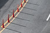 Yellow Double Dividing Line And Red Plastic Warning Poles Over Gray Highway Asphalt poster