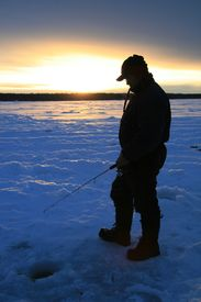picture of ice fishing  - a man ice fishing in the evening in Canada - JPG